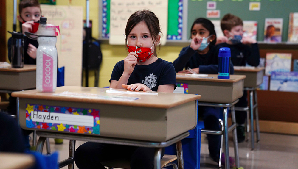 Schoolchildren swab and test themselves for COVID-19 to prevent the spread of the coronavirus disease (COVID-19) in the classroom at South Boston Catholic Academy in Boston, Massachusetts, January 28, 2021. Allison Dinner   Reuters