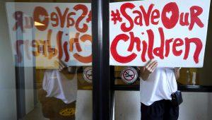 Un manifestante sostiene una pancarta frente a las ventanas de la oficina central del distrito escolar unificado de Los Ángeles, el jueves 9 de septiembre de 2021, en Los Ángeles. (AP Foto/Damian Dovarganes)
