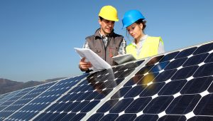 Man showing solar panels technology to student girl. | PHOTO: Shutterstock