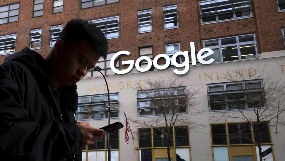 En esta foto del 17 de diciembre del 2018, un hombre con un celular pasa por delante de las oficinas de Google en la ciudad de Nueva York. Google planea adquirir la Terminal St. John en Nueva York por 2.100 millones de dólares, para hacer el sitio el eje de su campus en Hudson Square. (AP Foto/Mark Lennihan)