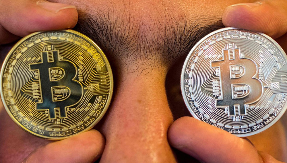 """A picture taken on February 6, 2018 shows a person holding a visual representation of the digital cryptocurrency bitcoin, at the """"Bitcoin Change"""" shop in the Israeli city of Tel Aviv. 