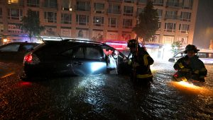 Members of the FDNY rescue a woman from her stalled car due to flash flooding in New York, Wednesday, September 1. (Anthony Behar/Sipa/AP Images)