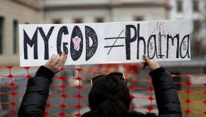"""Fotografía de archivo del 13 de enero de 2020 de una mujer sosteniendo un letrero durante una protesta frente al Congreso de Nueva Jersey, en Trenton. El letrero lee """"Mi Dios no es lo mismo que las farmacéuticas"""". (AP Foto/Seth Wenig, Archivo)"""
