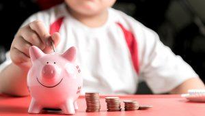 Photo: Hand boy put coin to piggy bank, saving money. | Shutterstock