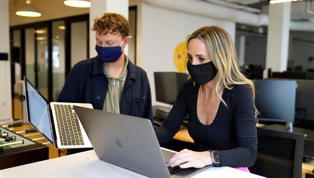 Kelly Soderlund (der) consulta con un colega en las oficinas de la firma TripActions de San Francisco el 27 de agosto del 2021. (AP Photo/Eric Risberg)