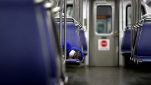 A person rests on a Washington Metro subway car wearing a face mask, following Mayor Muriel Bowser's declaration of a state of emergency due to the coronavirus disease (COVID-19) in Washington, U.S., April 13, 2020. REUTERS/Tom Brenner