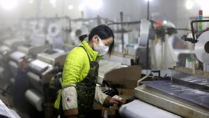 In this Feb. 27, 2020 photo, a woman works on a spinning mill in a textile factory in Hangzhou in eastern China's Zhejiang Province. (Chinatopix via AP)