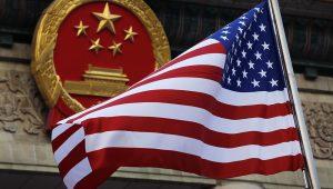 En esta foto del 9 de noviembre del 2017, se ve una bandera estadounidense junto al emblema nacional de China en una ceremonia de bienvenida a visitantes estadounidenses. (AP Foto/Andy Wong)