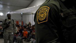 A Customs and Border Patrol officer stands near migrants at the Donna Soft-Sided Processing Facility in Donna, Texas, U.S. July 12, 2019. Picture taken July 12, 2019. REUTERS/Veronica G. Cardenas