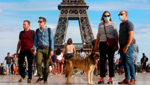 Tourists wear protective masks while visiting the Eiffel Tower on August 2 in Paris, France.   Mehdi Taamallah/NurPhoto/AP