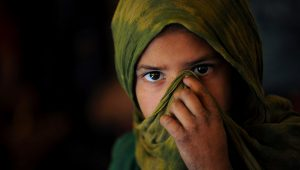 An Afghan Kuchi (Pashtun nomad) girl covers her face as she attends a class on October 27, 2010. She is being taught in a tent near the ruins of the Darul Aman Palace on the outskirts of Kabul. SHAH MARAI/AFP/Getty Images